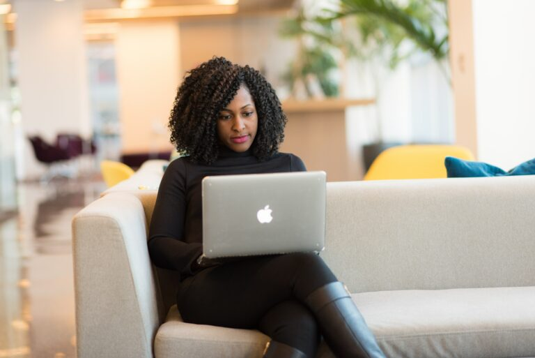 Black woman sitting on sofa working from laptop