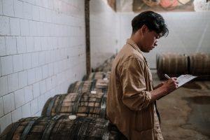 Person filling in checklist in wine cellar