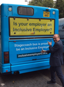 Richard pointing at the Inclusion Week branded bus