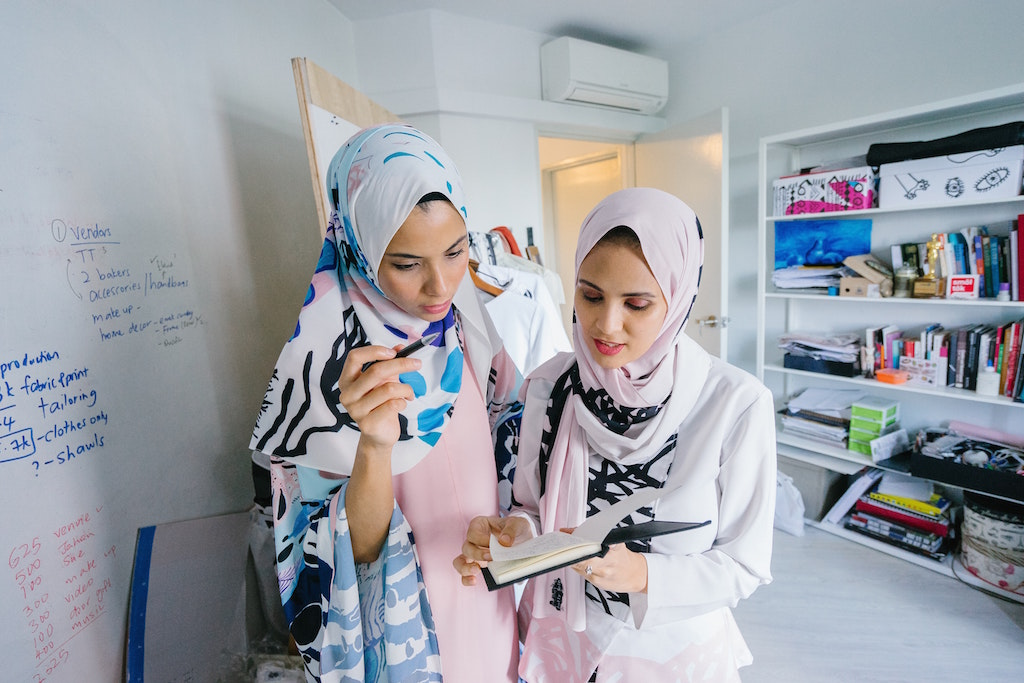 2 hijabi women completing an impact assessment