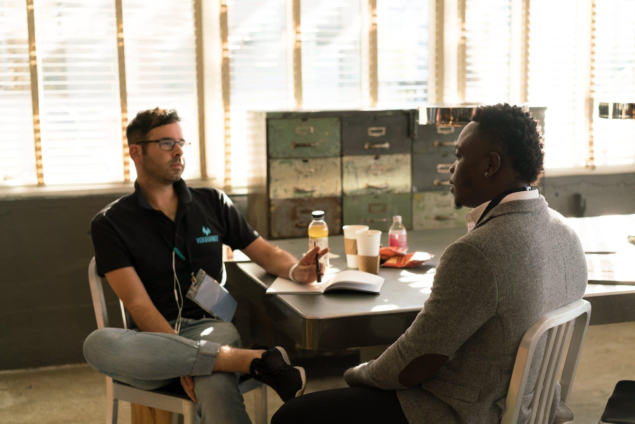 A black and a white man having a discussion around a table