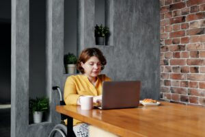 Woman in wheelchair sitting at desk with laptop