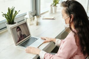 Woman in face mask having a zoom call
