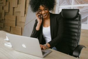 Black woman working on laptop talking on the phone