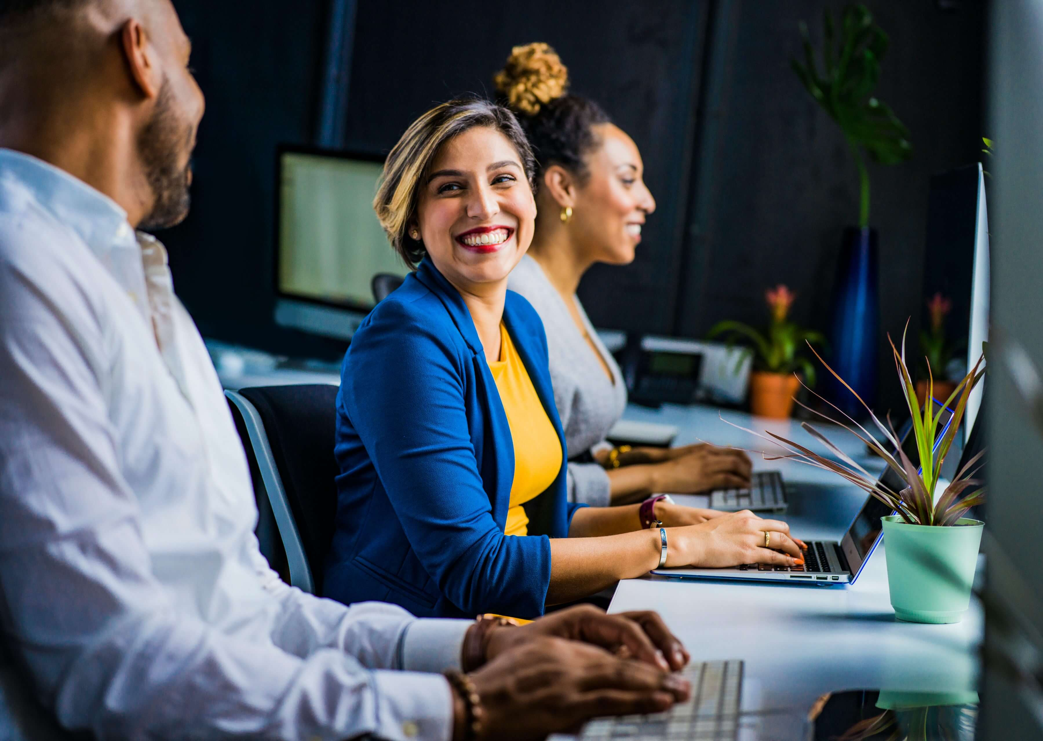 Woman in blue vest smiling and sitting between her colleagues