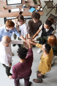 People of various ethnicities forming a group huddle