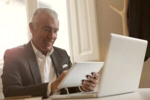 Older man working at laptop and tablet