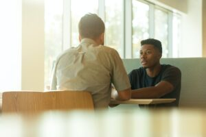 Two young men having a face to face conversation at a table