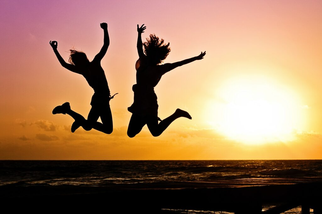 Two women jumping with their arms in the air