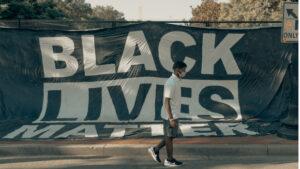 Man walking in front of Black Lives Matter flag