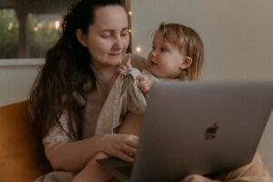 Working mum on laptop with child