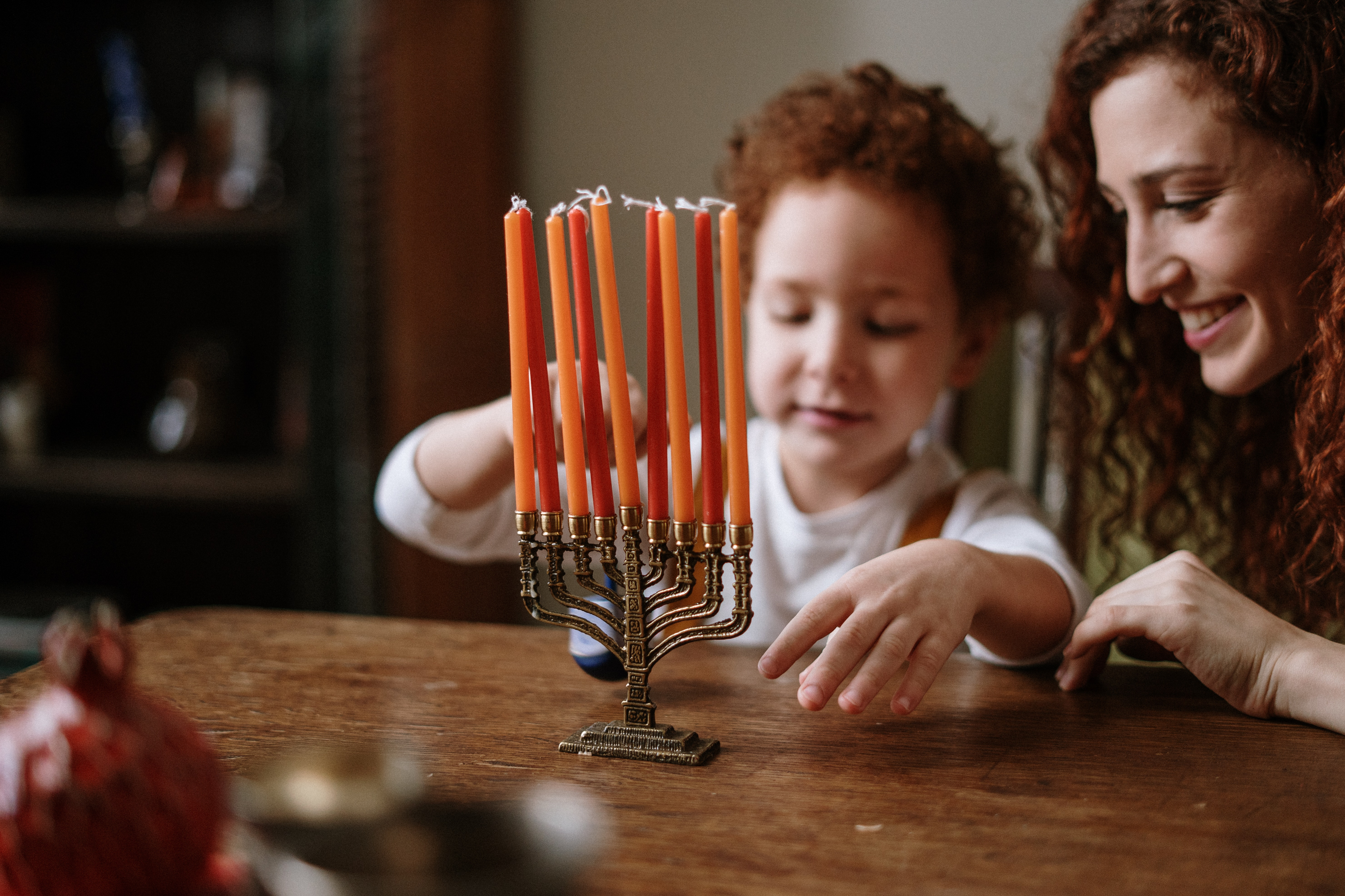 Mother and child look at a Menorah