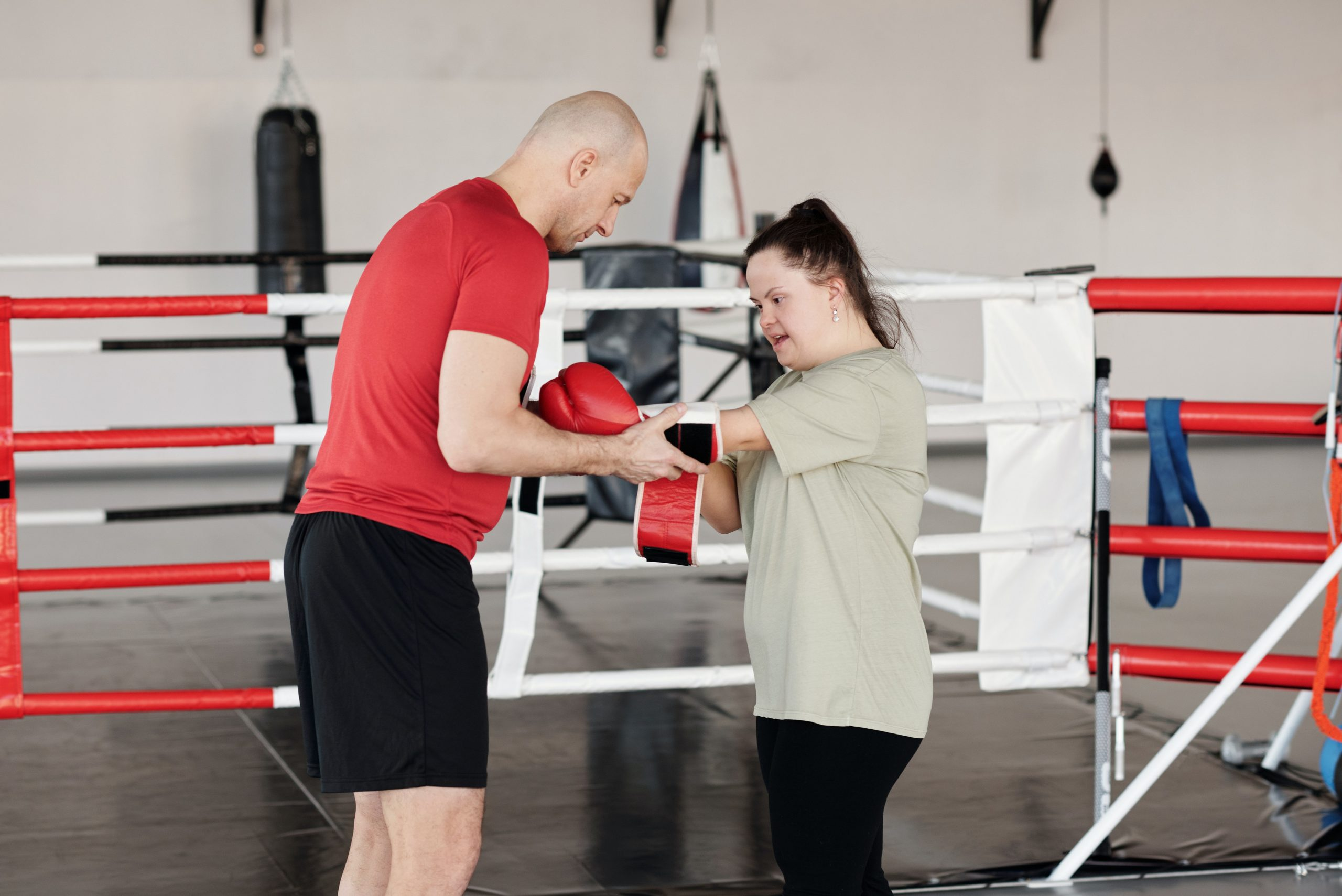Boxer helping boxer with downs syndrome put on their glove