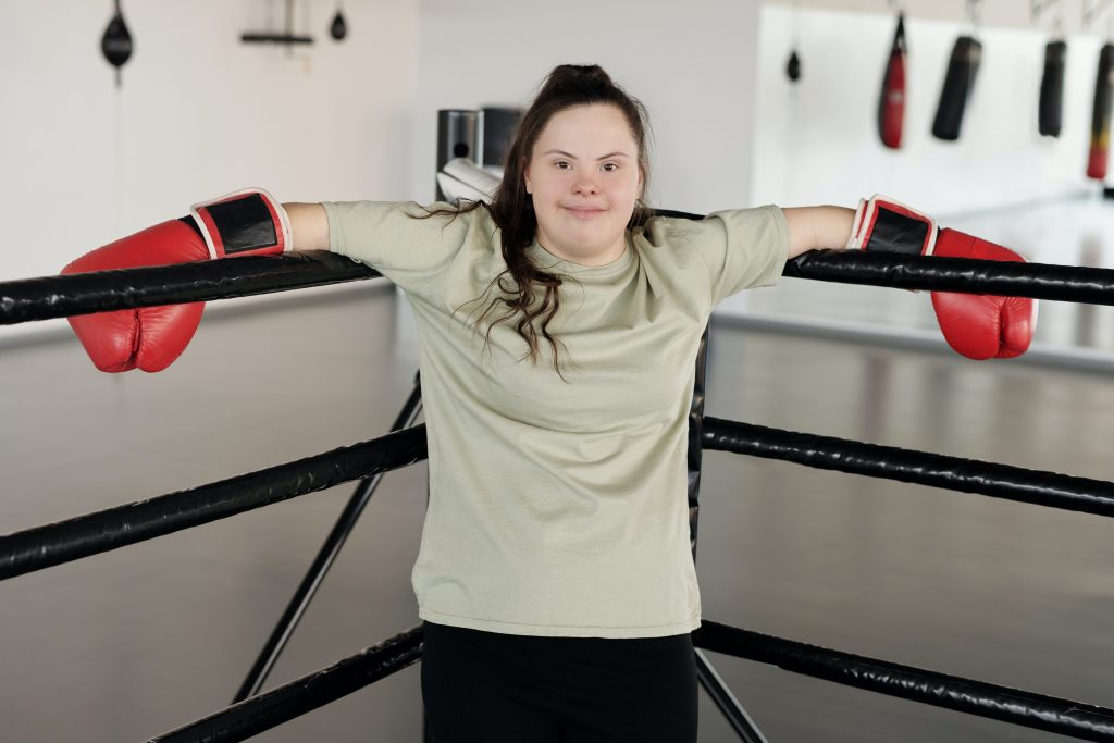 Girl with downs syndrome posing with boxing gloves in boxing ring