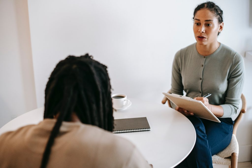 Line manager taking notes during meeting with employee to discuss mental health