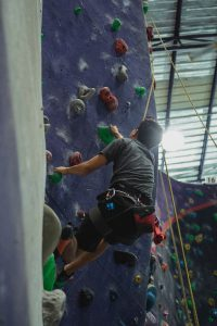 Person going up climbing wall