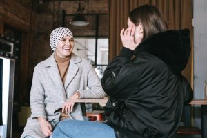 Person with cancer having a chat with a friend