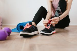 Person tying their shoes while sitting amongst a yoga mat and training equipment at home