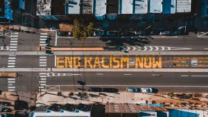 Bird's eye view of road with the letters 'End racism now' painted in yellow letters