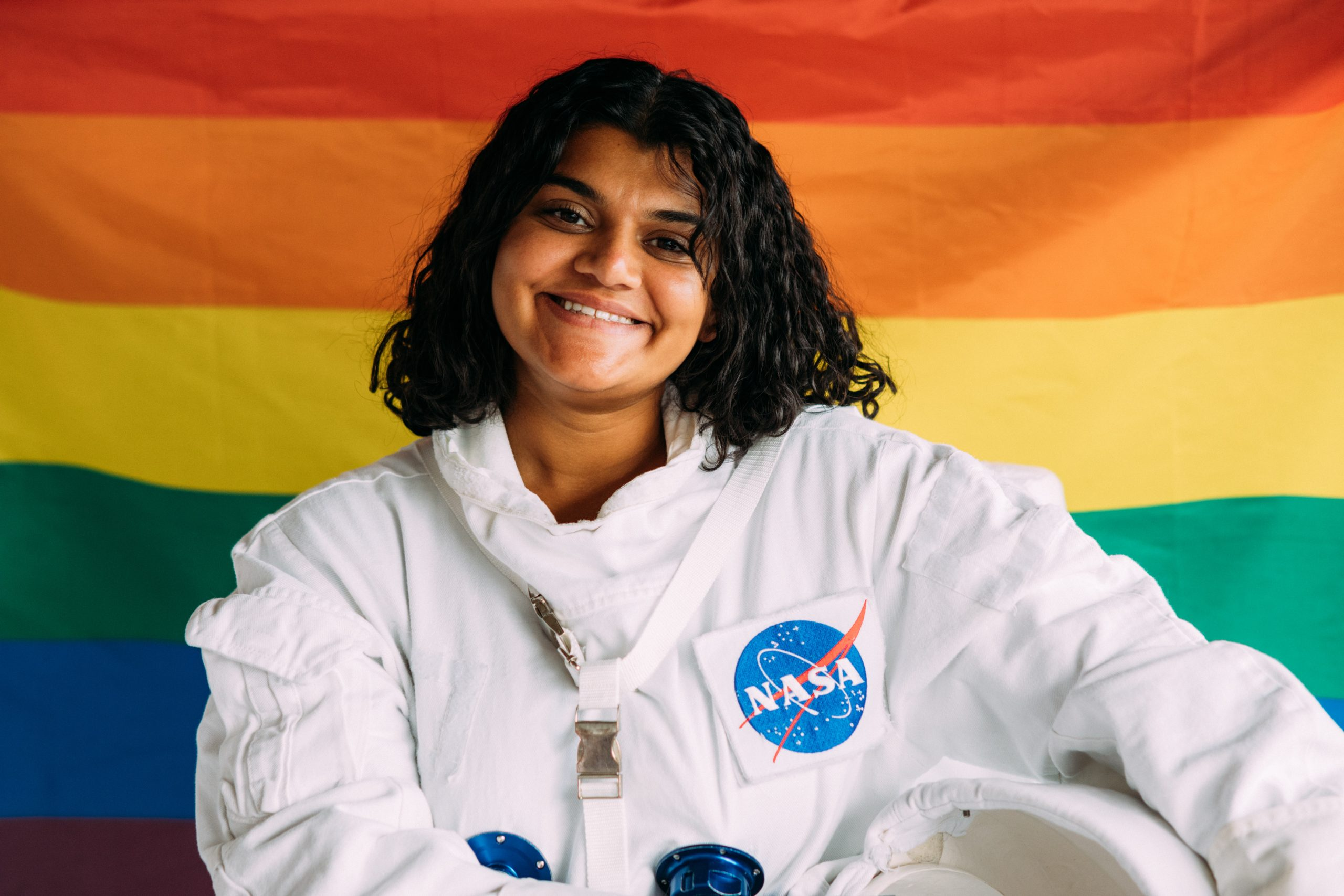 Person in an astronaut suit standing in front of LGBT flag