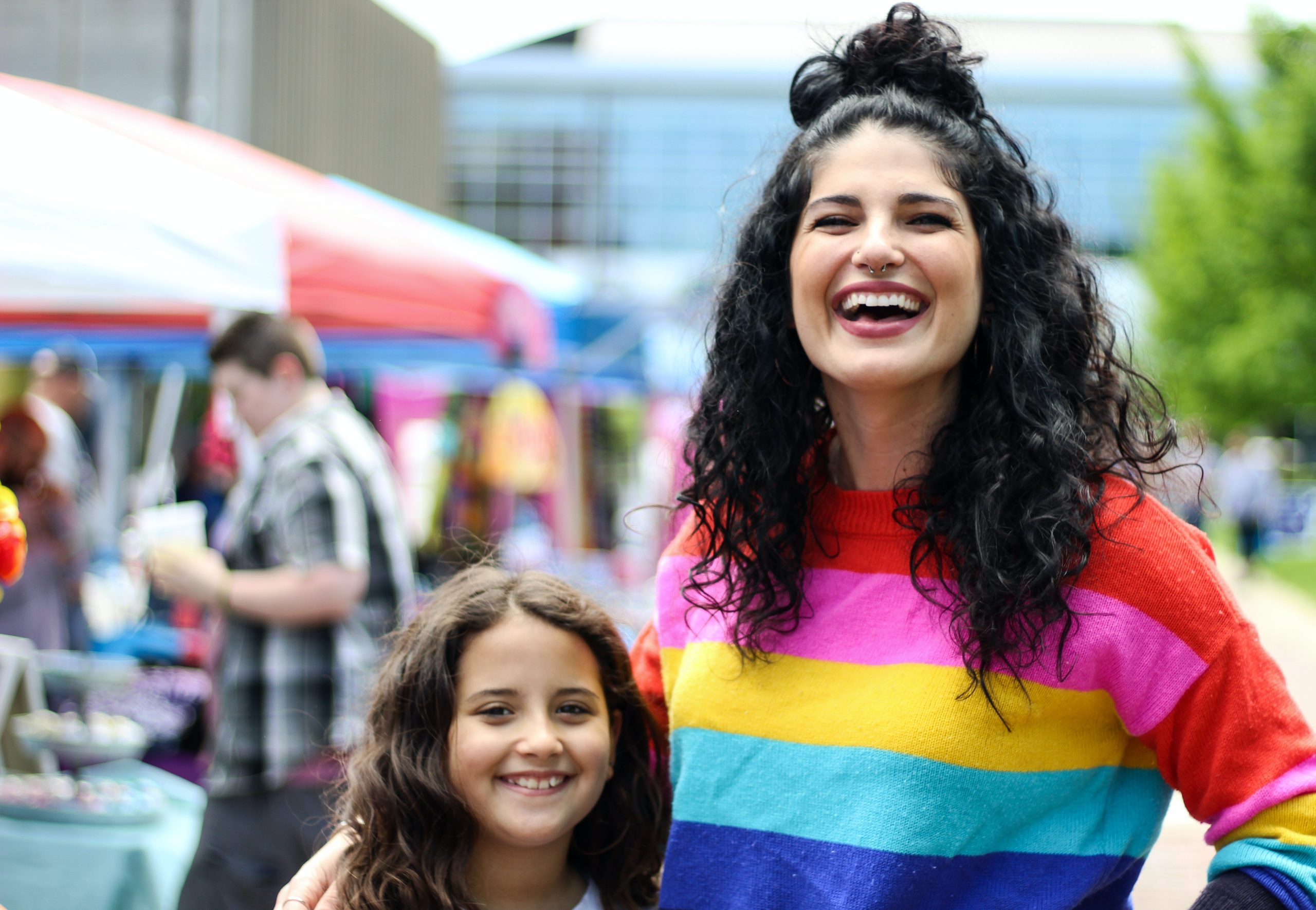Mother wearing rainbow pride jumper while attending pride with their child