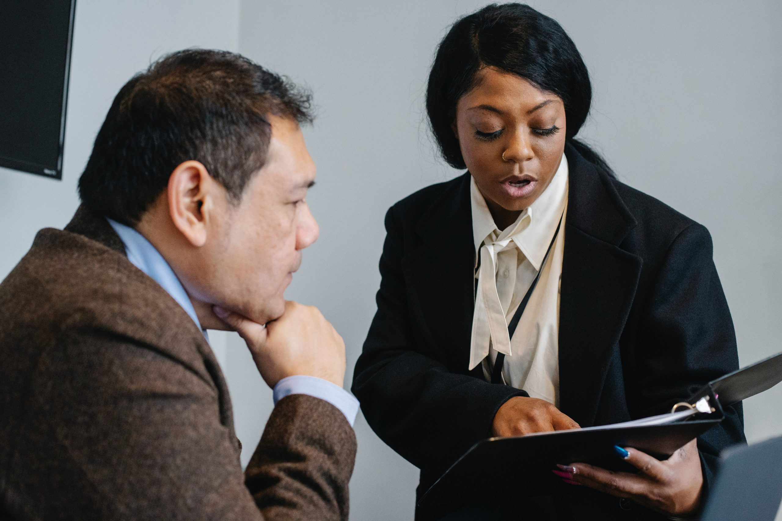 Line manager pointing at document in their binder, while their colleague listens to their briefing