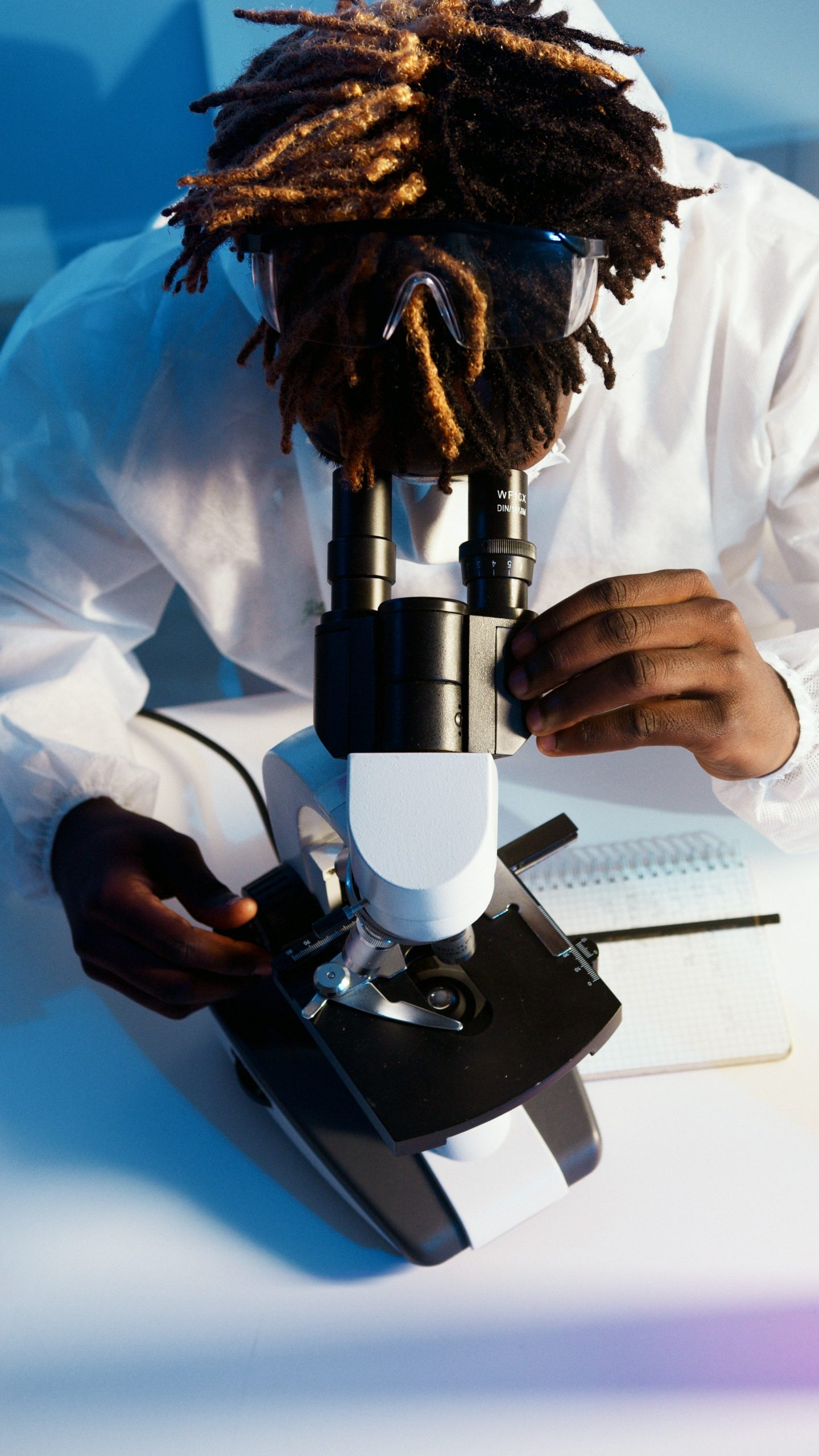 Black male scientist looking into microscope