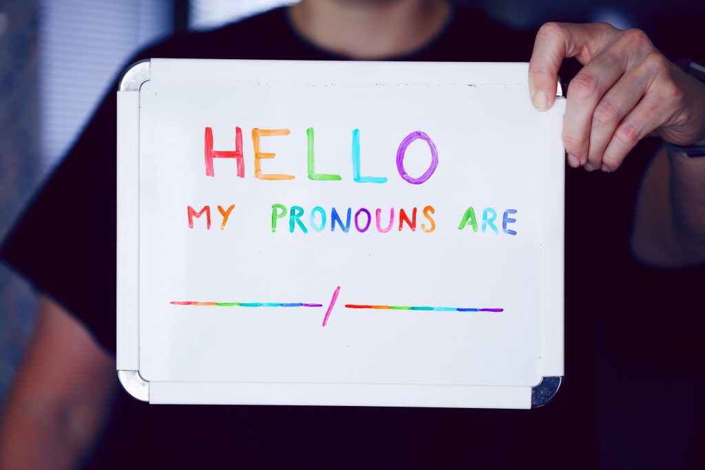 """Person holding up a sign that says: """"My pronouns are..."""""""