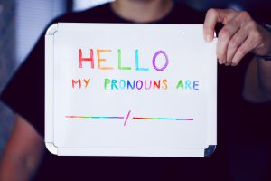 "Person holding up a sign that says: ""My pronouns are..."""
