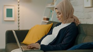 Pregnant woman wearing a headscarf sitting on the sofa working on her laptop