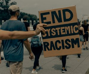 protestors marching, the image if focused on a placard that reads 'End Systemic Racism'