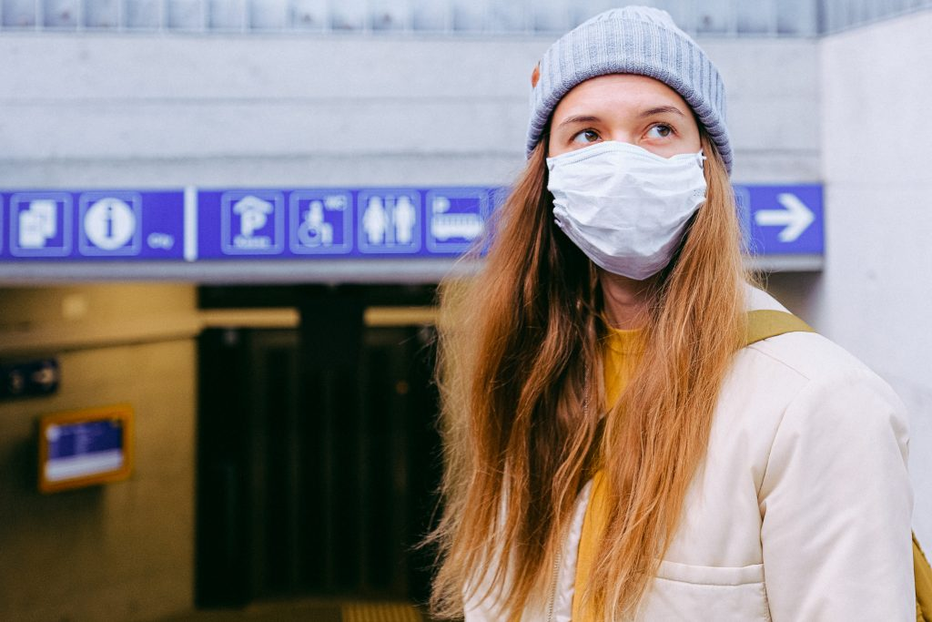 Woman travelling on the underground while wearing a mask