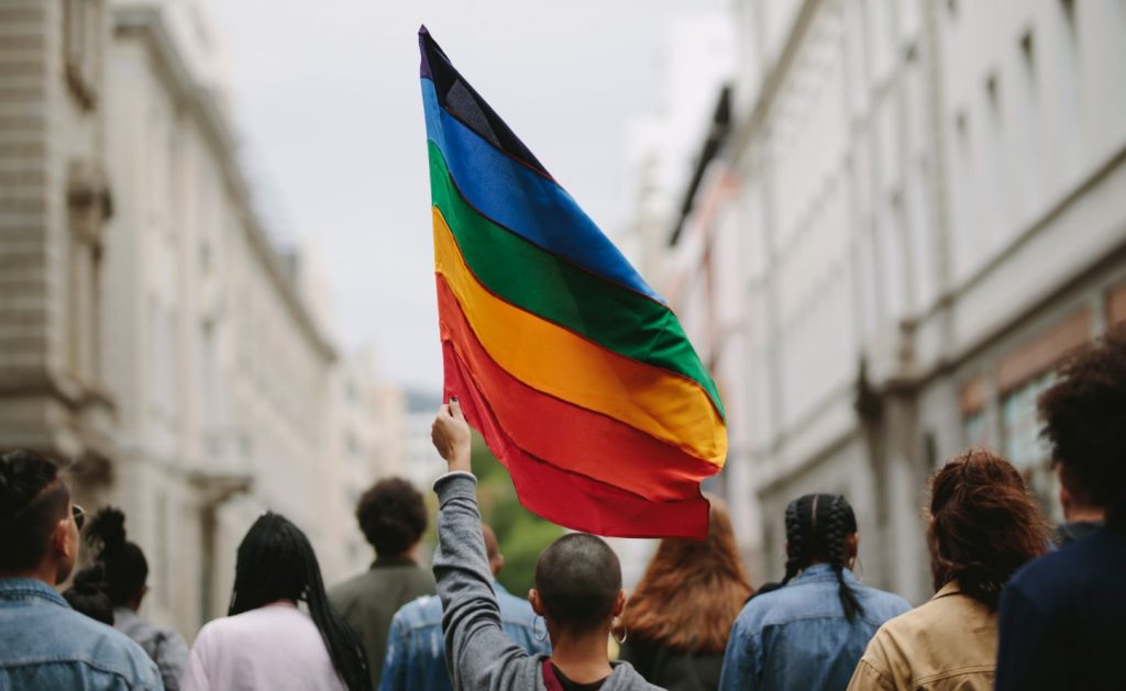 Person holding up Pride flag among crowd of participants