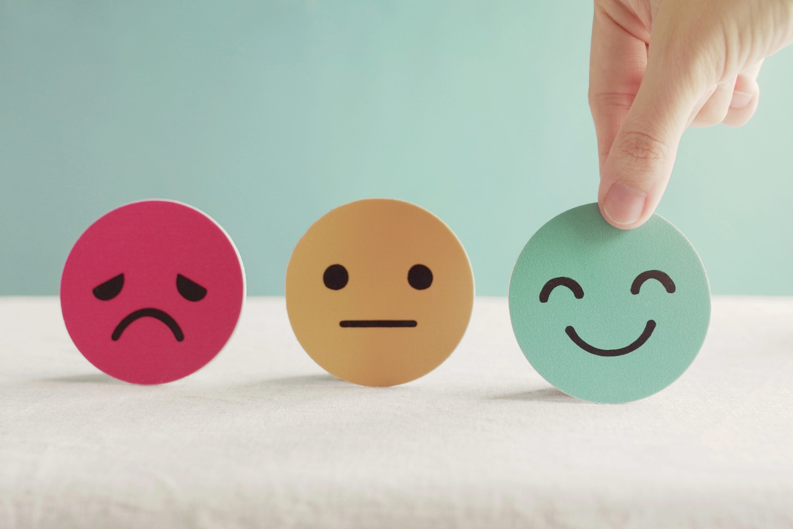 Person pointing towards three emojis, one frowning, one with a blank expression and one smiling