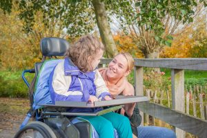Young person in a wheelchair talking to an older woman who is knelt beside her, they are outside