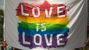 The words 'Love is Love' written on a white sheet painted over a rainbow flag
