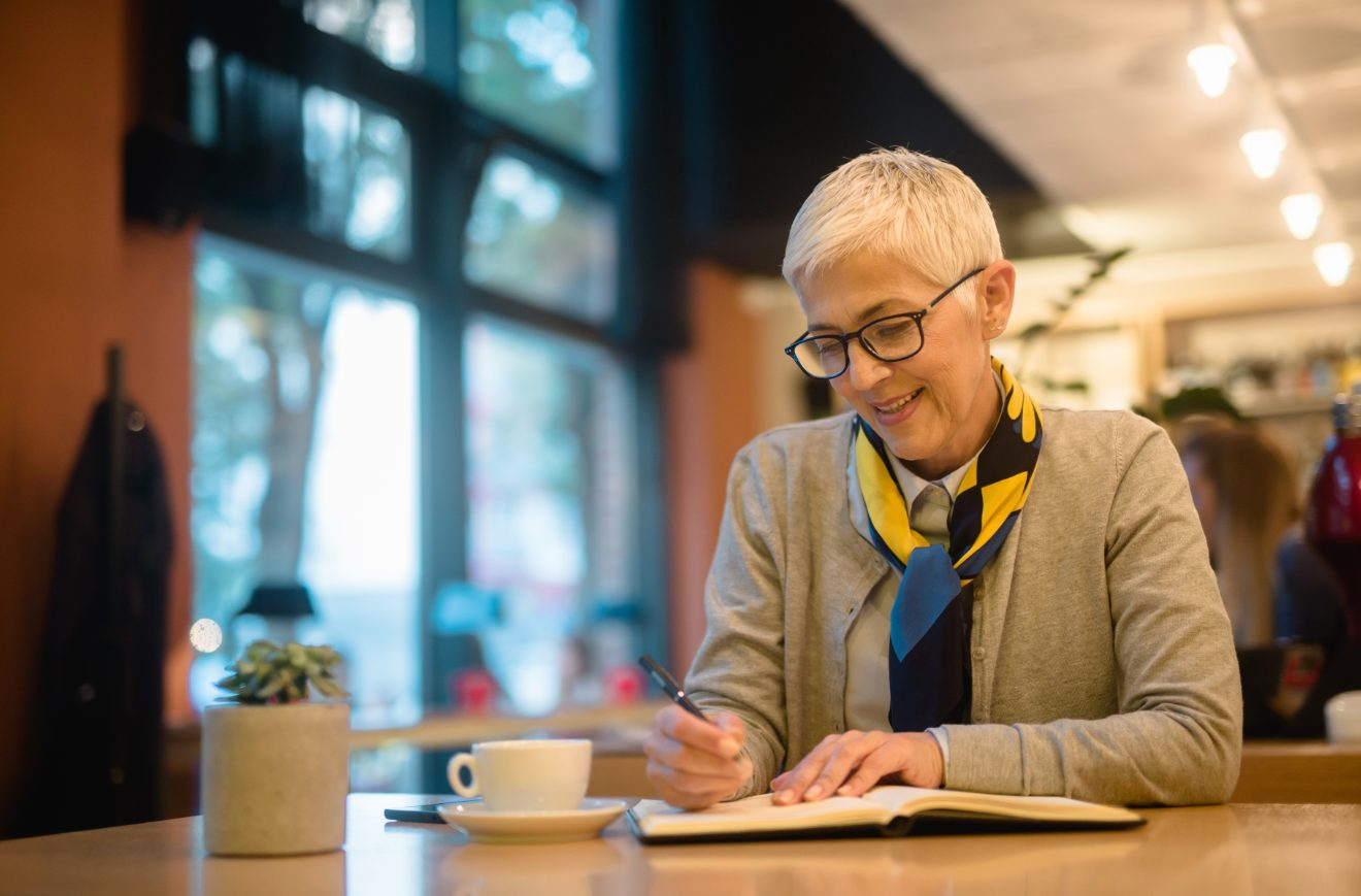 Older woman writing in a notepad