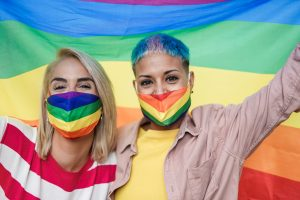 Couple celebrating pride while holding up the flag and wearing pride masks