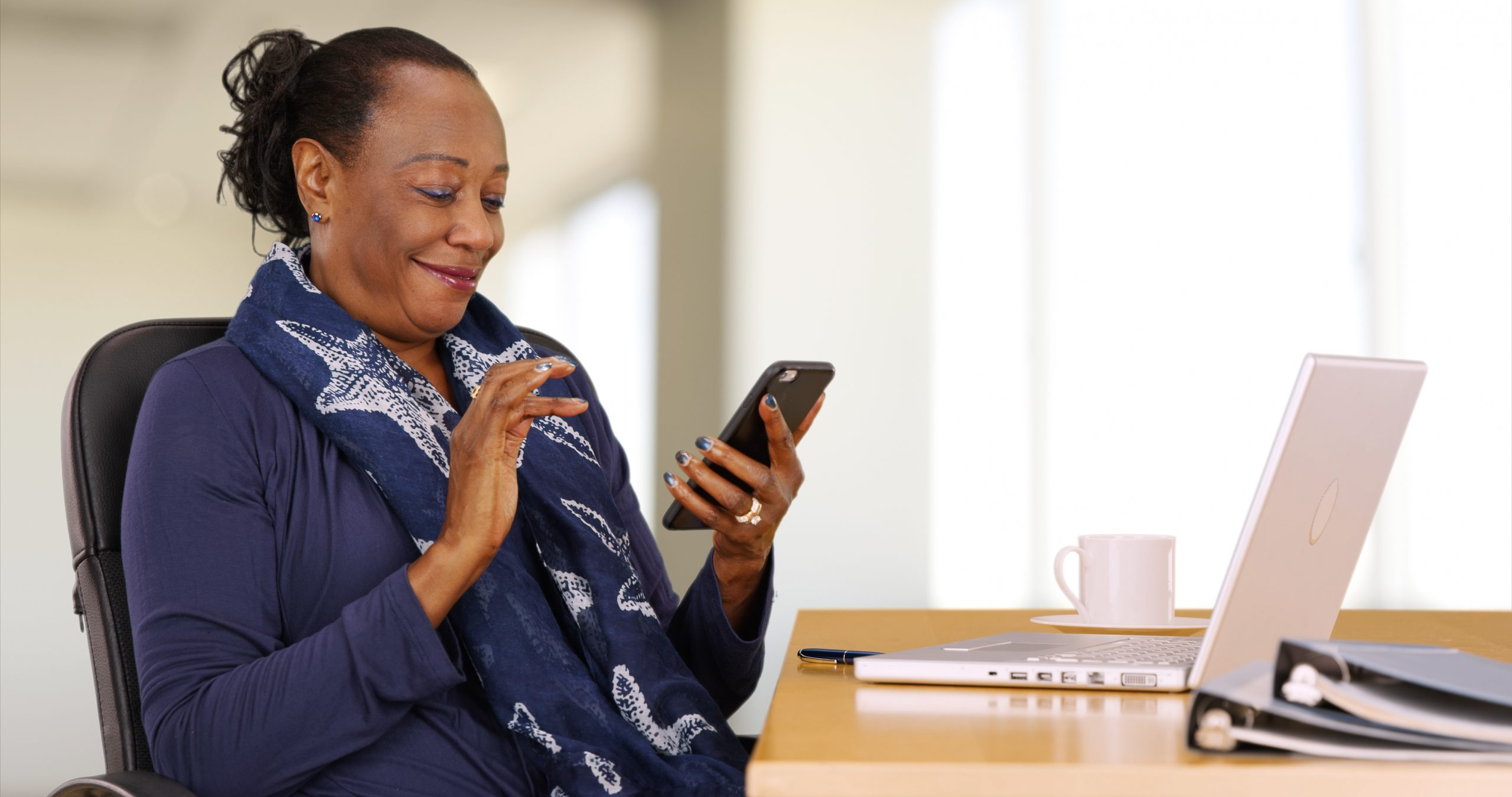 Older office woman at work desk communicating with colleagues via text message