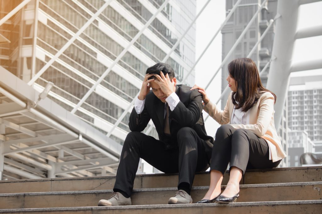 Office worker comforting grieving employee, who is holding their head in their hands