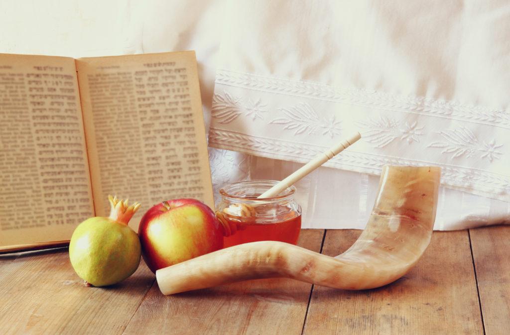 Shofar, torah book, honey, apple and pomegranate over wooden table.
