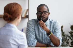 Man pondering what his colleague has told him about inclusion