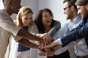 Diverse group of office workers doing a high five